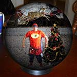 Christmas Spherical Puzzle Featuring Chuckman Flying With Santa, Reindeer, And Sled, And Chuckman Beside A Christmas Tree Advertisement