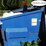 The Feet Of Chuckman, An Online Comic Superhero, Are Seen Sticking Out Of A Dumpster