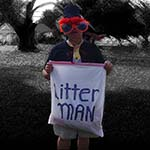 A Man Wearing A Hat And Red Clown Wig Holding A Plastic Bag Labeled Litter Man